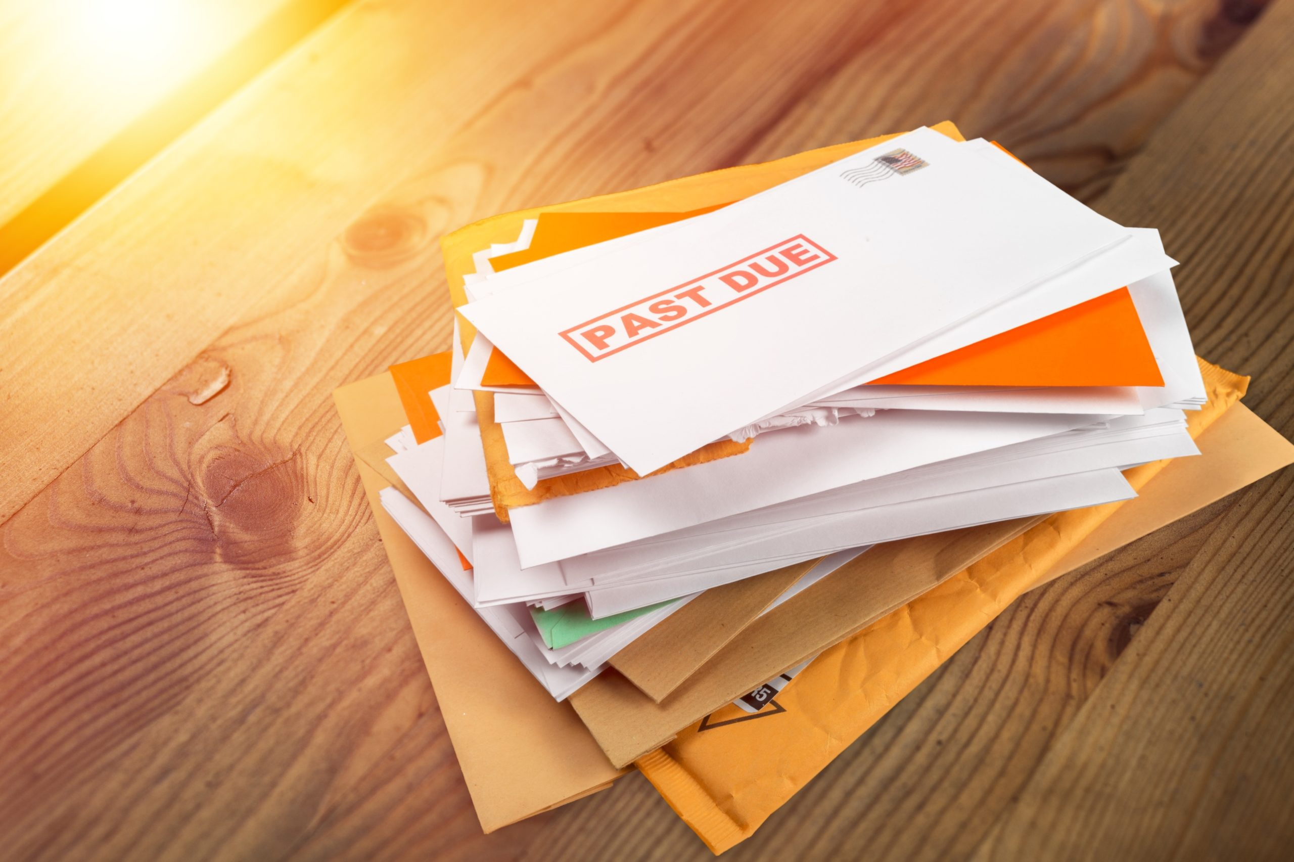 Pile of envelopes with overdue utility bills on the desk